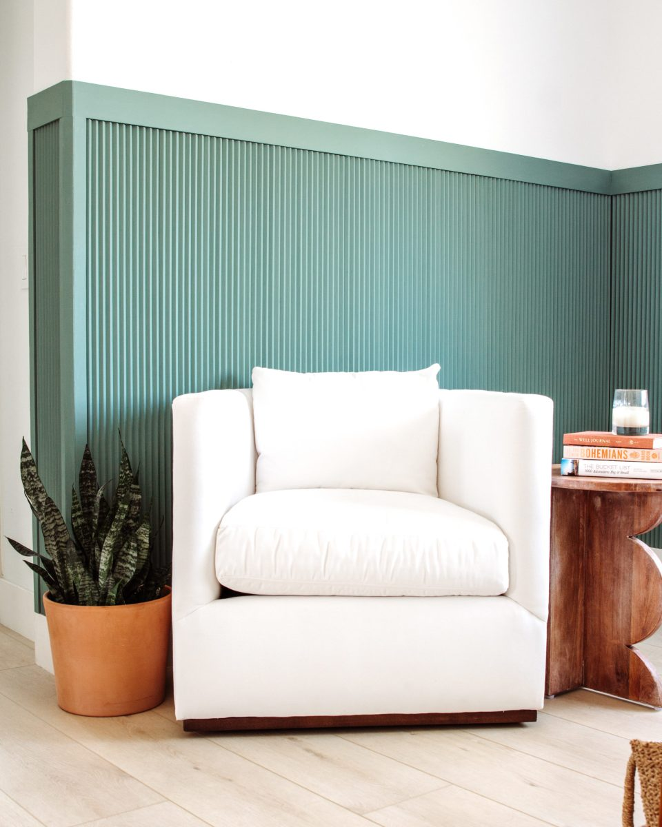 a crisp white upholstered armchair sits in between a snake plant and a funky side table