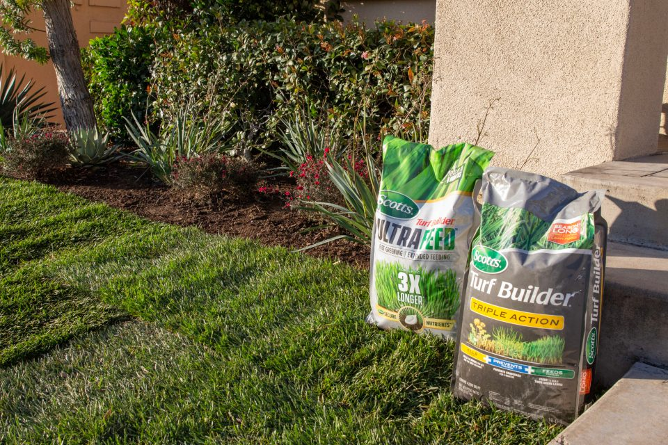 A freshly sodded yard with bags of fertilizer near the landscaping