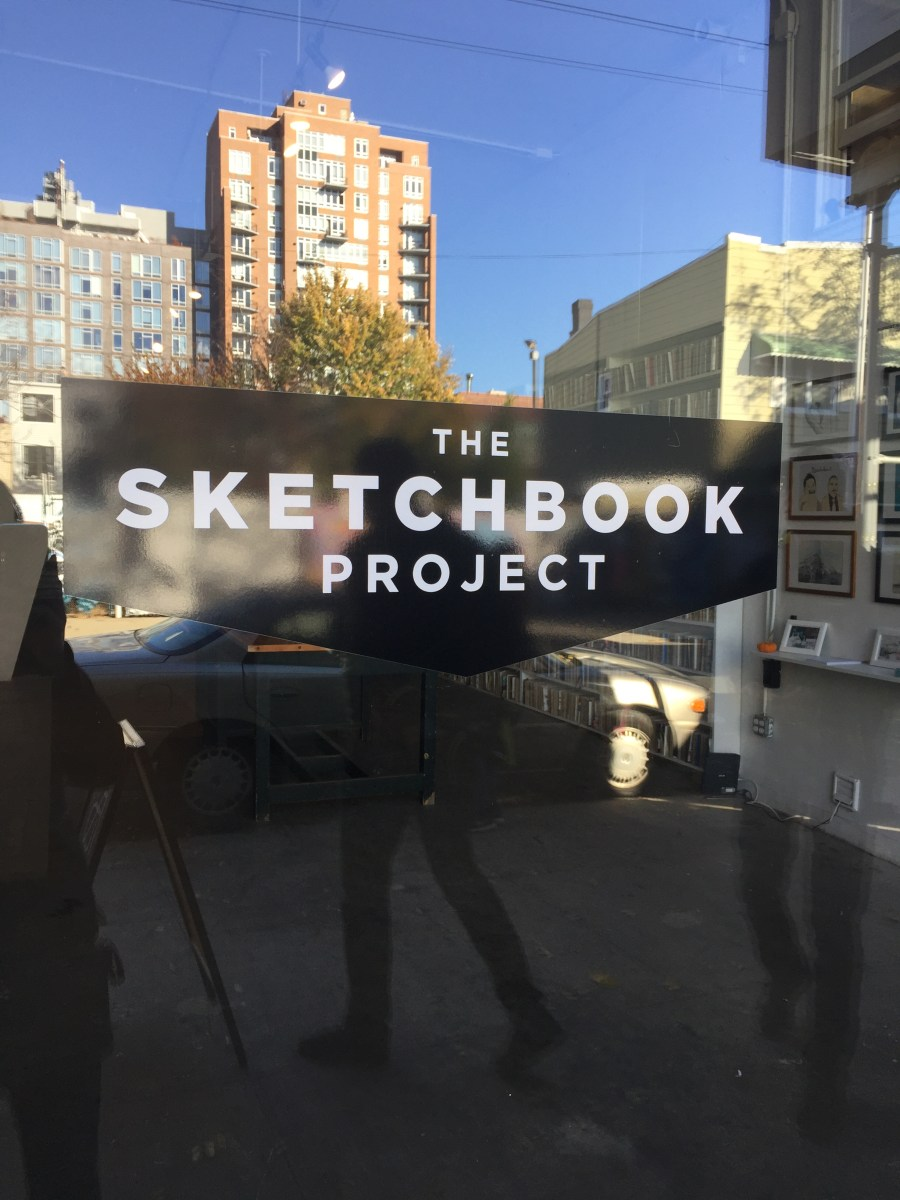 """Photo of door to the Brooklyn Art Library showing the name of the project """"The Sketchbook Project"""" as well as reflections of the buildings and people in front of the door."""