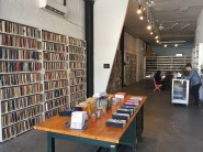 Interior of a library showing shelves full of sketchbooks. Man standing behind the counter and person sitting on a chair viewing a book.