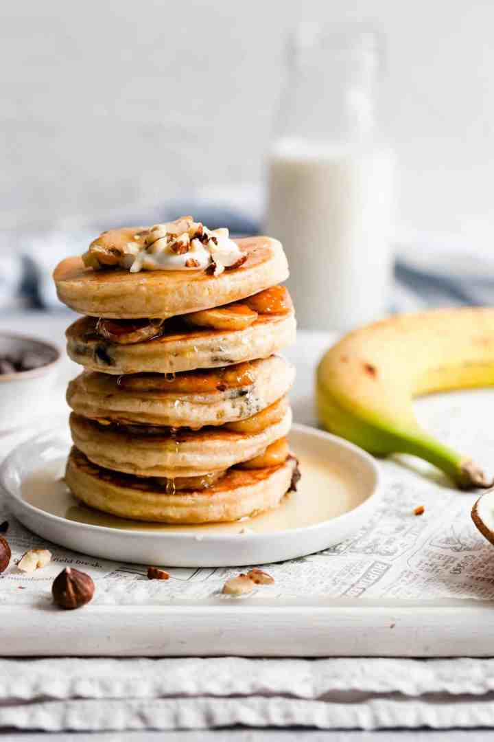 side view of stack of pancakes with maple syrup