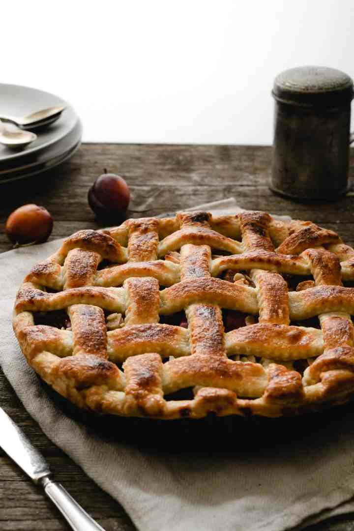 Plum pie with almonds on the kitchen table