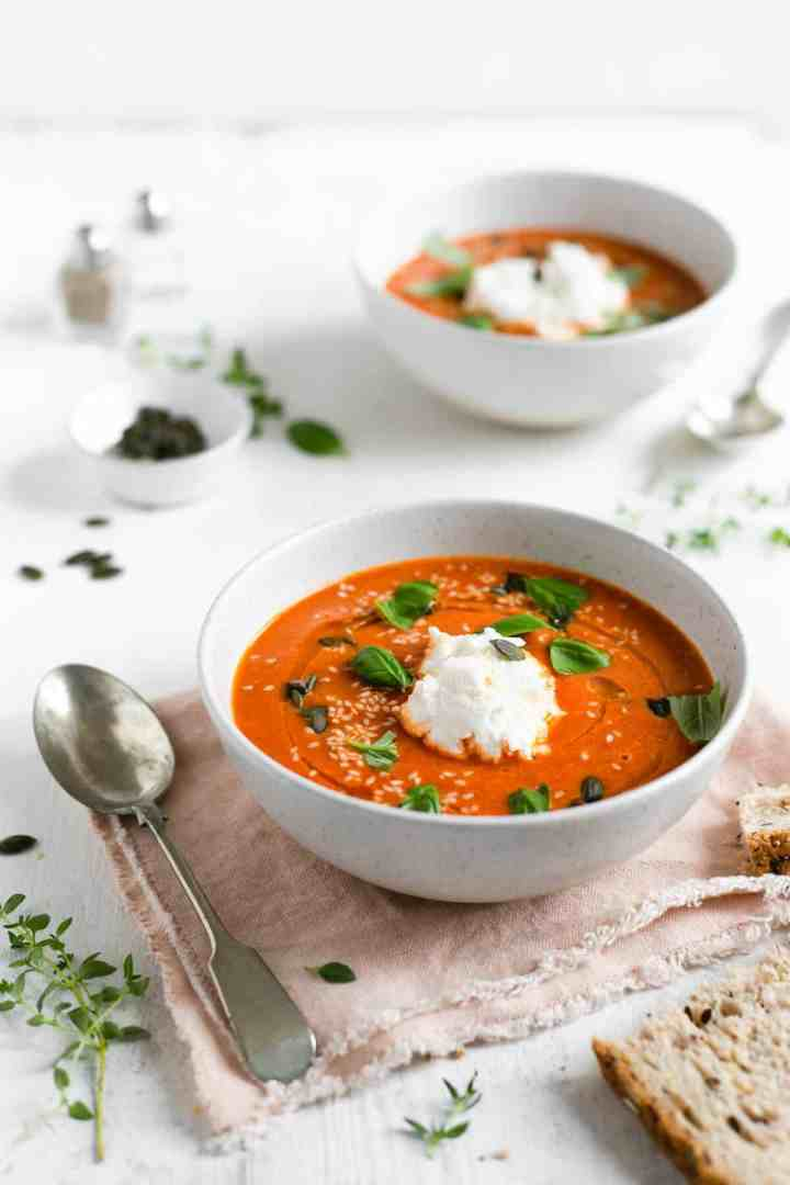 Two bowls of roasted tomato soup topped with sesame and pumpkin seeds