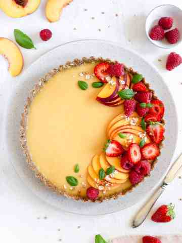 Vegan peach tart with gluten-free crust, topped with summer berries