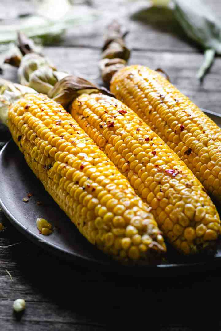 Three large corn cobs in chilli butter on a plate