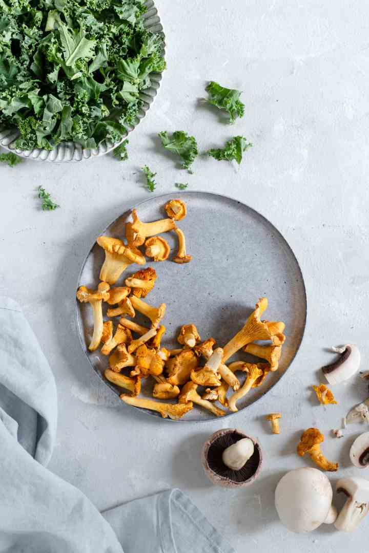Plate with fresh curly kale and plate with chanterelle mushrooms