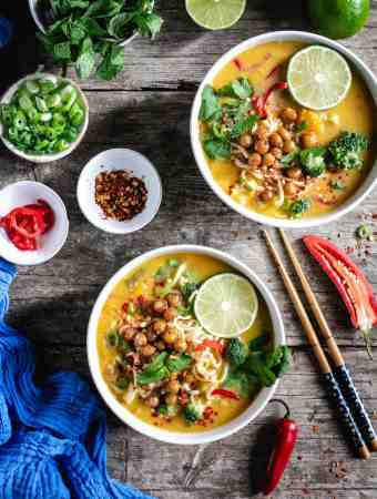 Overhead shot of two bowls of Thai style pumpkin laksa topped with roasted chickpeas and fresh mint