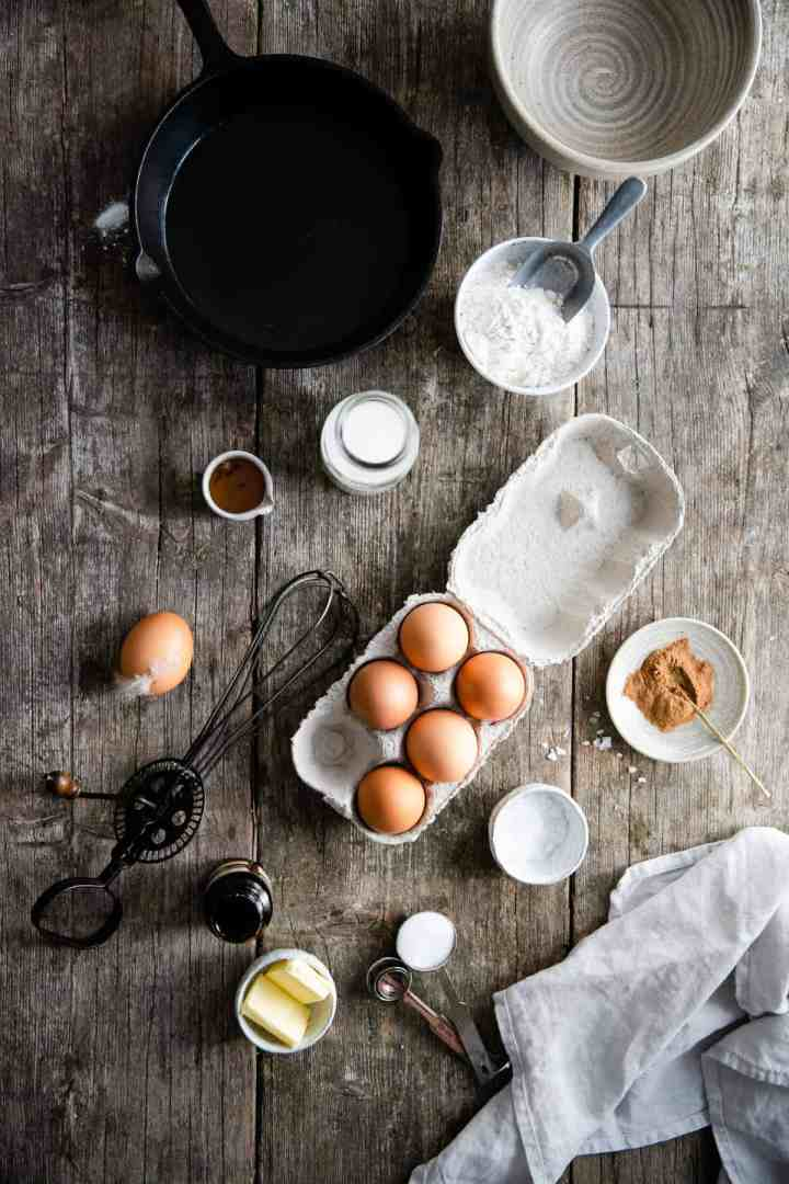 Overhead shot of ingredients on the table for mixed berry Dutch baby (eggs, flour, butter, sugar, cinnamon, milk)