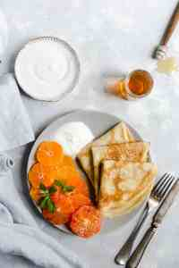 a plate with three crepes folded into triangles with slices of citrus and some yogurt