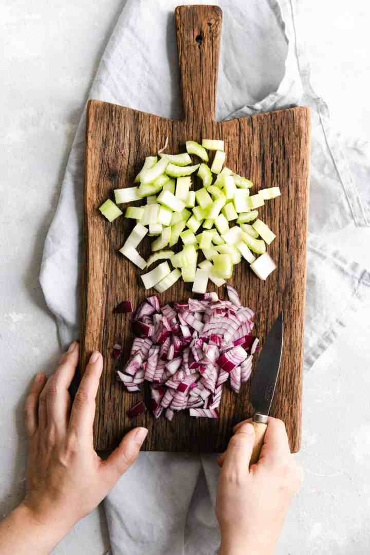 Overhead shot of chopped celery and onion on a wooden chopping board