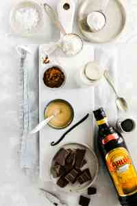 Overhead shot of the ingredients for the vegan chocolate pudding: dark chocolate, coffee liquor, condensed coconut milk, almond milk, cocoa, cornflour, salt and vanilla
