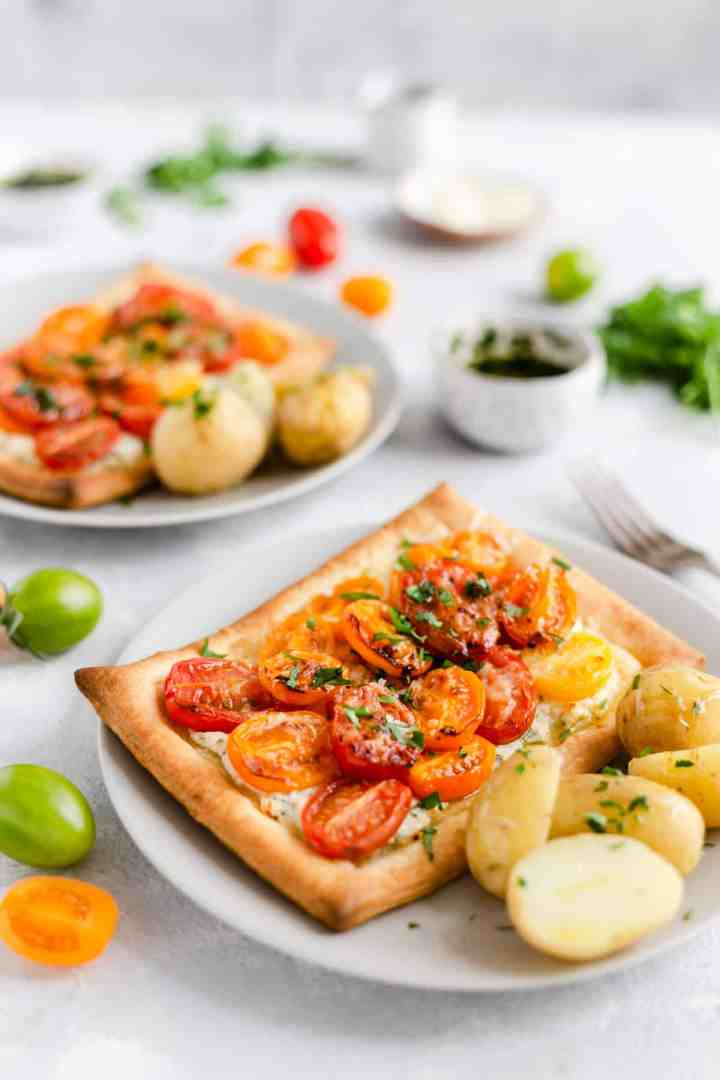 side shot of single mixed tomato and cheese tartlet with some cooked new potatoes