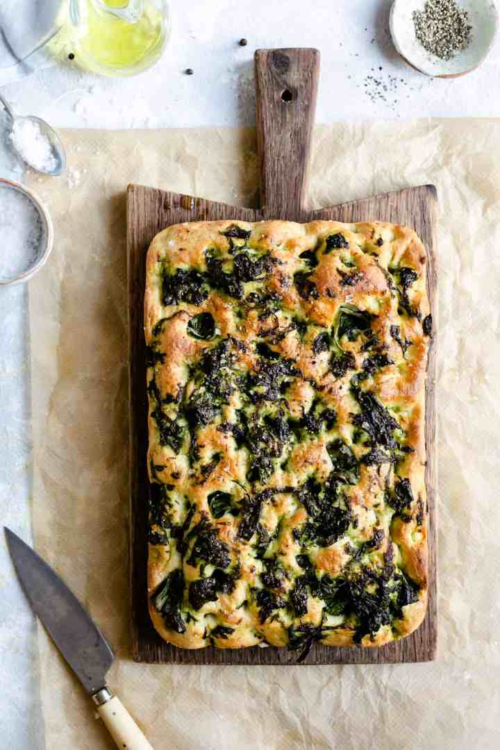 Overhead shot of a whole baked wild garlic and black pepper focaccia on a wooden chopping board with small knife on side