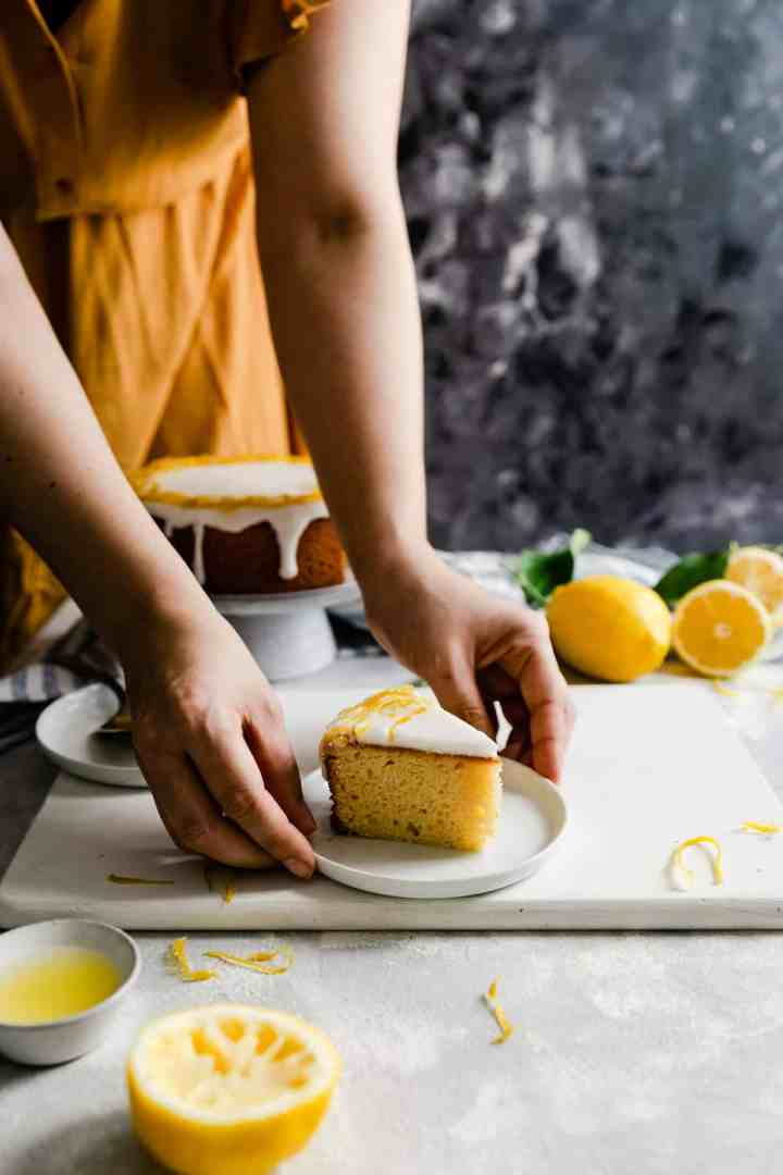 a side angle shot of a person holding a small plate with a slice of a lemon cake
