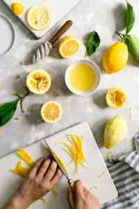 overhead shot of a person slicing lemon peel on a white chopping board surrounded with lemon halves
