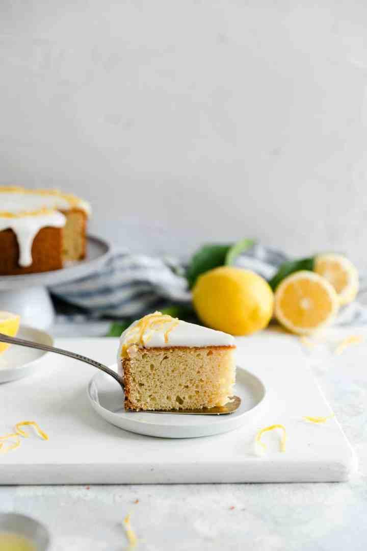 a side angle shot of one slice of zesty lemon cake on a small plate