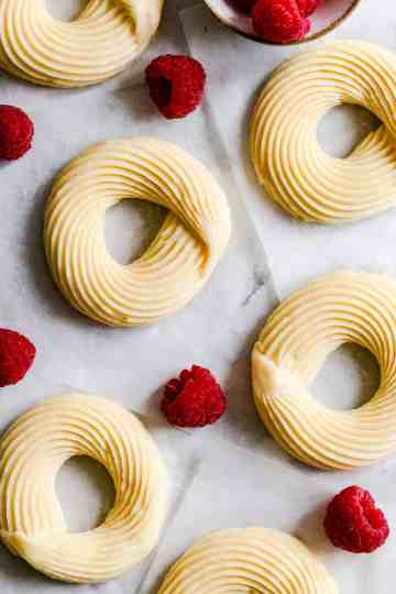 top view close up of raw cruller doughnuts with some raspberries around
