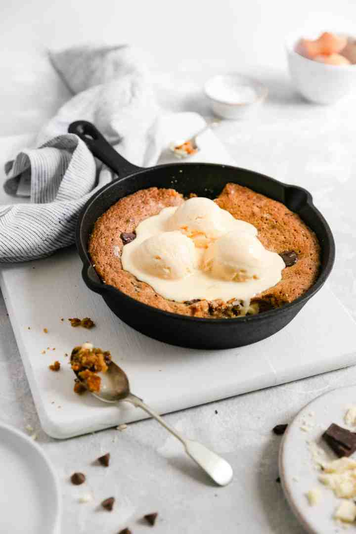a side shot of a skillet with chocolate chip and malted milk cookie inside topped with vanilla ice cream