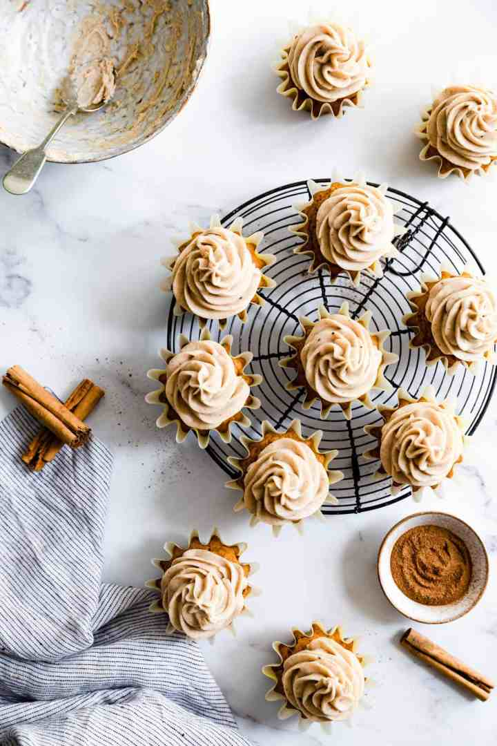Pumpkin and chai cupcakes arranged on a round cooling rack