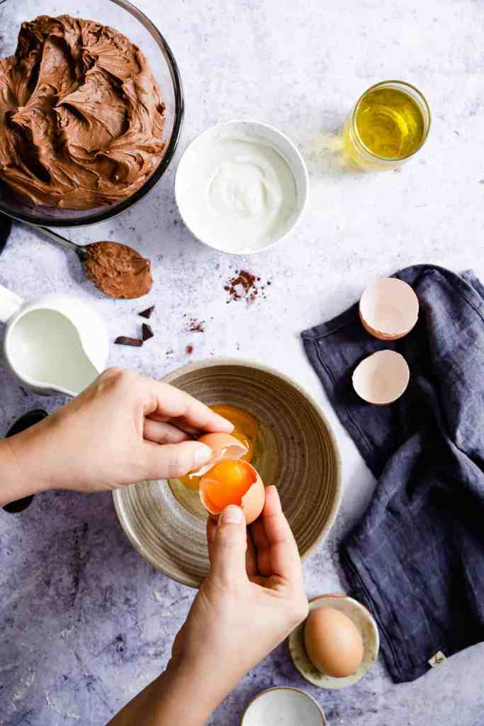 top view of a person cracking some eggs into the bowl