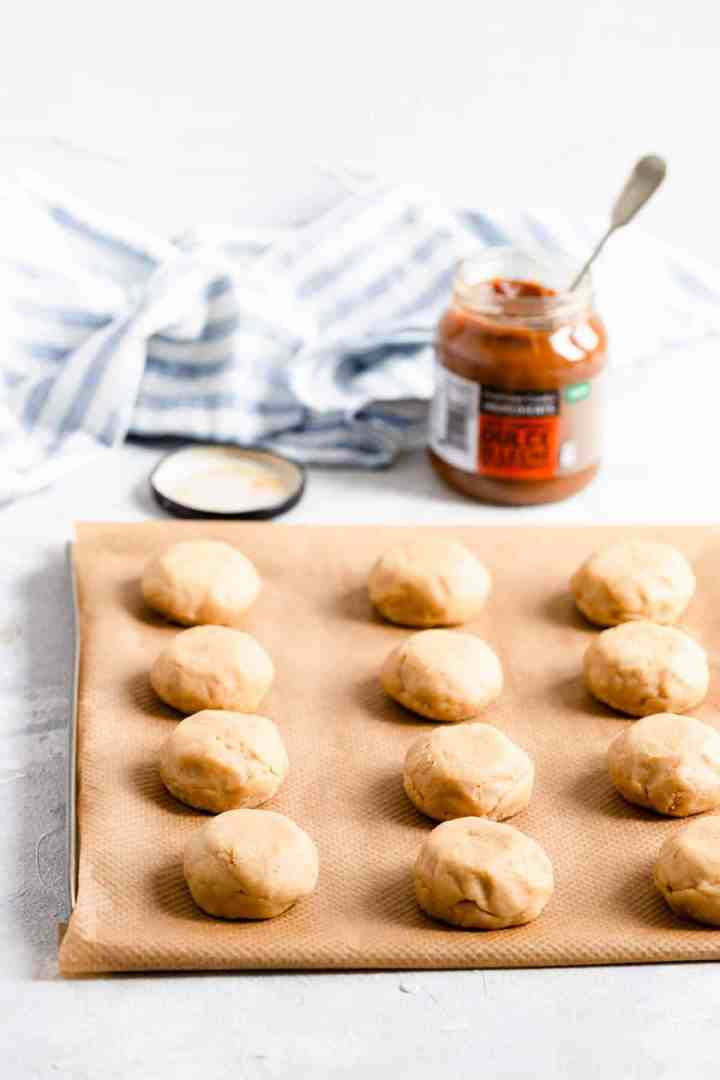 a side shot of raw cookie dough balls on a baking tray