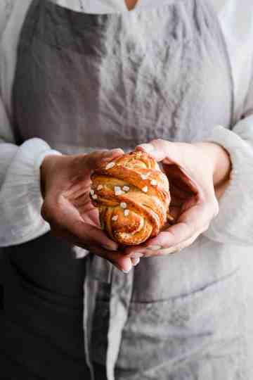 close up of a person holding cardamom bun