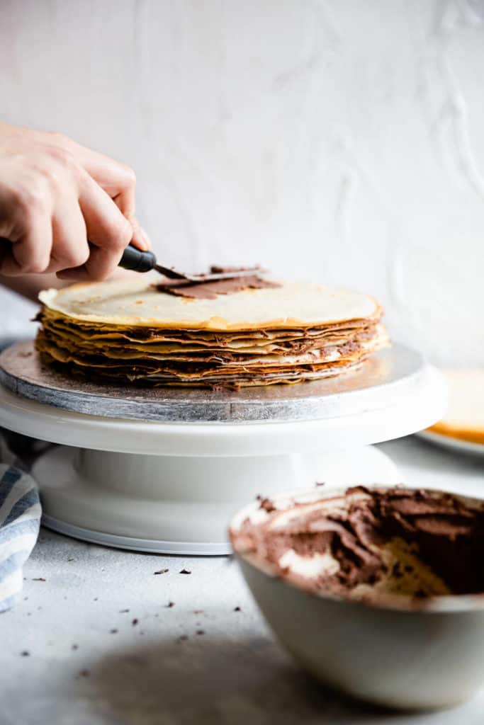 chocolate cream being spreaded over the stack of crepes