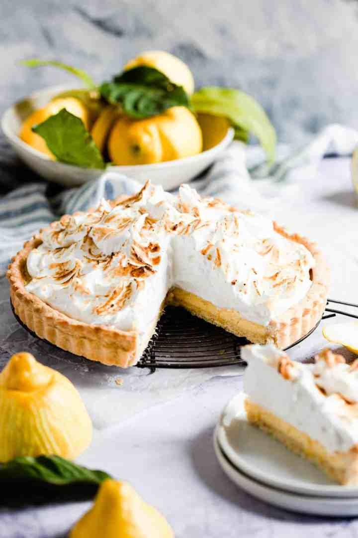 side view of a lemon pie with a slice cut out