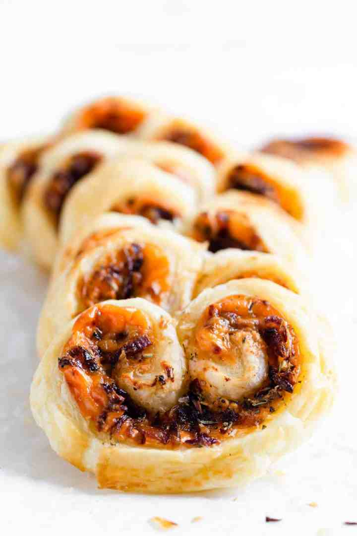 super close up of cream cheese and caramelised onion palmiers on white surface