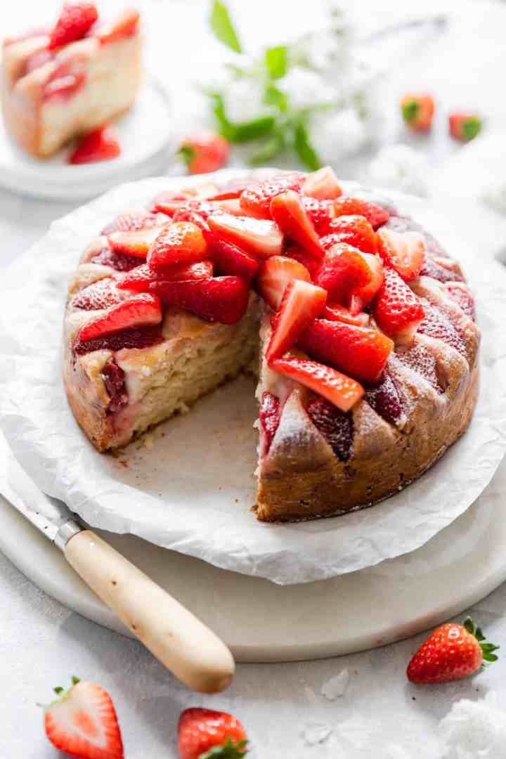 top side angle of fresh strawberry yogurt cake with slice cut out