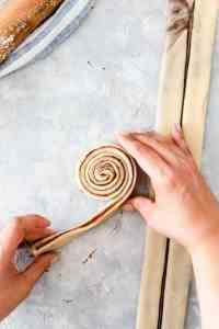 overhead shot of strip of dough being rolled into swirl