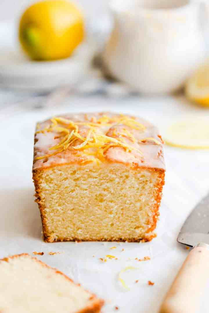 straight ahead shot of lemon drizzle cake with slice cut off