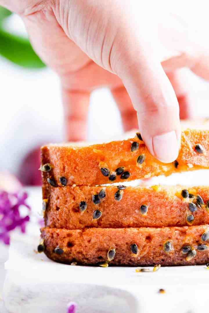 super close up of a hand lifting a slice of passion fruit loaf