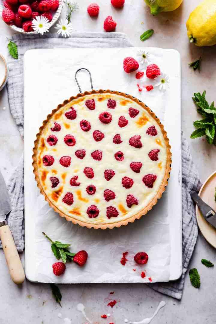 overhead shot of baked raspberry mascarpone tart on white board