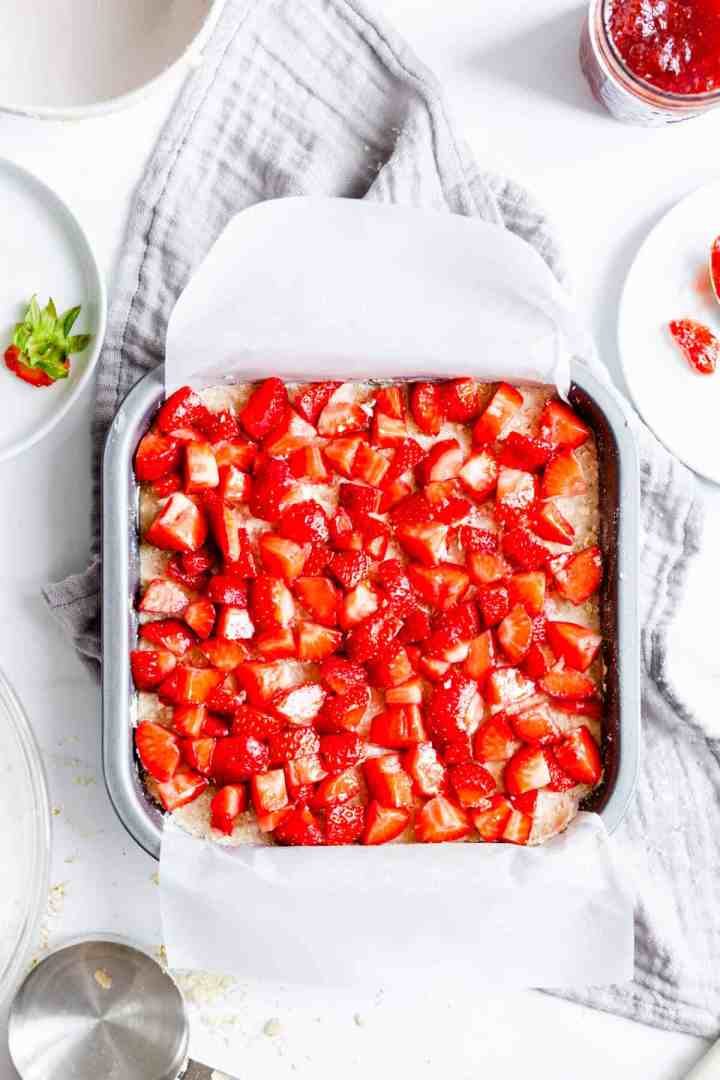 top view of a baking tin filled with crumble base and fresh strawberries