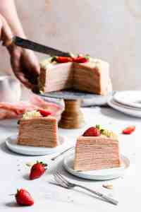 side shot of two slices of crepe cake and a person slicing the cake in the background