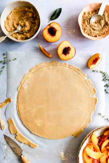 top view of peach galette crust rolled into a large circle