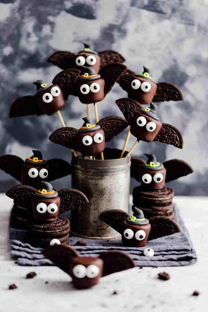 side angle of chocolate marshmallows looking like little bats on bamboo skewers