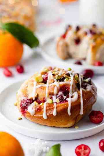 side super close up at orange and cranberry Chelsea bun with sugar glaze on top