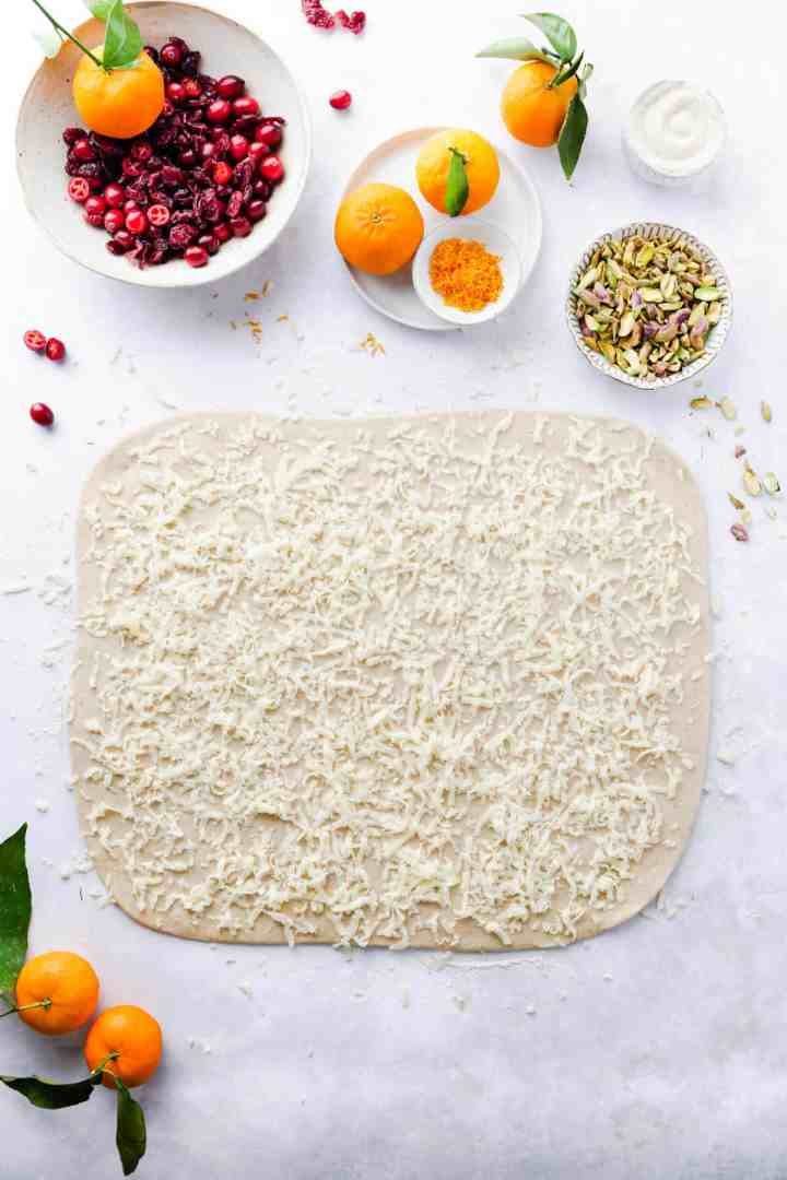 overhead shot of a dough rolled into rectangle and topped with grated marzipan
