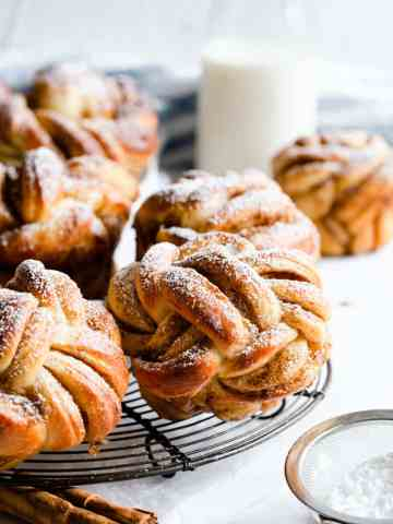 side shot of cinnamon buns shaped into knots and dusted with icing sugar