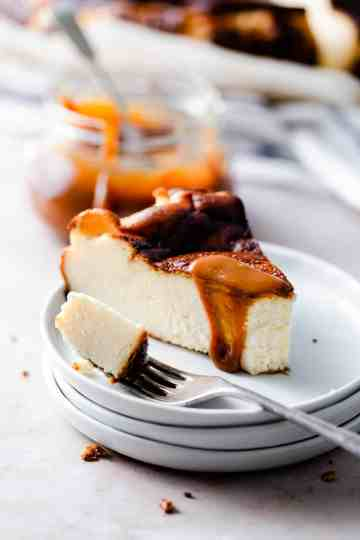 side angle close up of cheesecake wedge slice drizzled with caramel