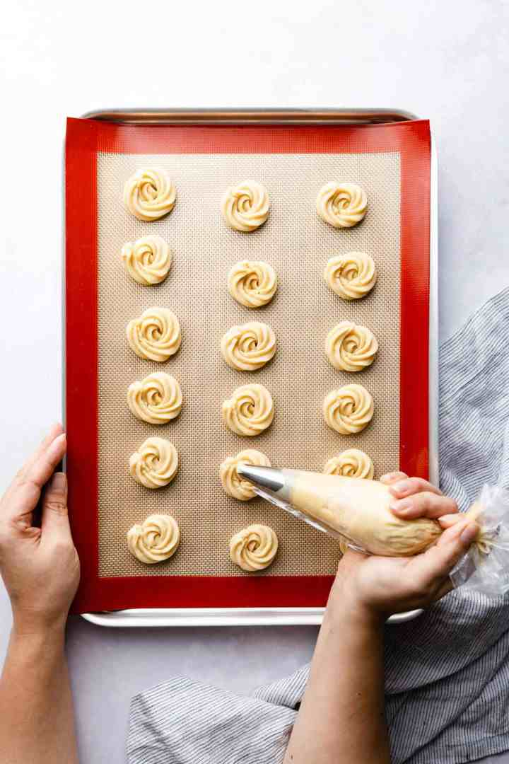 top view of a person piping the cookie dough onto baking tray with silicone mat