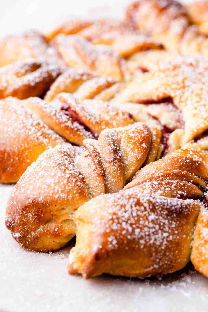 side angle super close up of raspberry star bread dusted with icing sugar