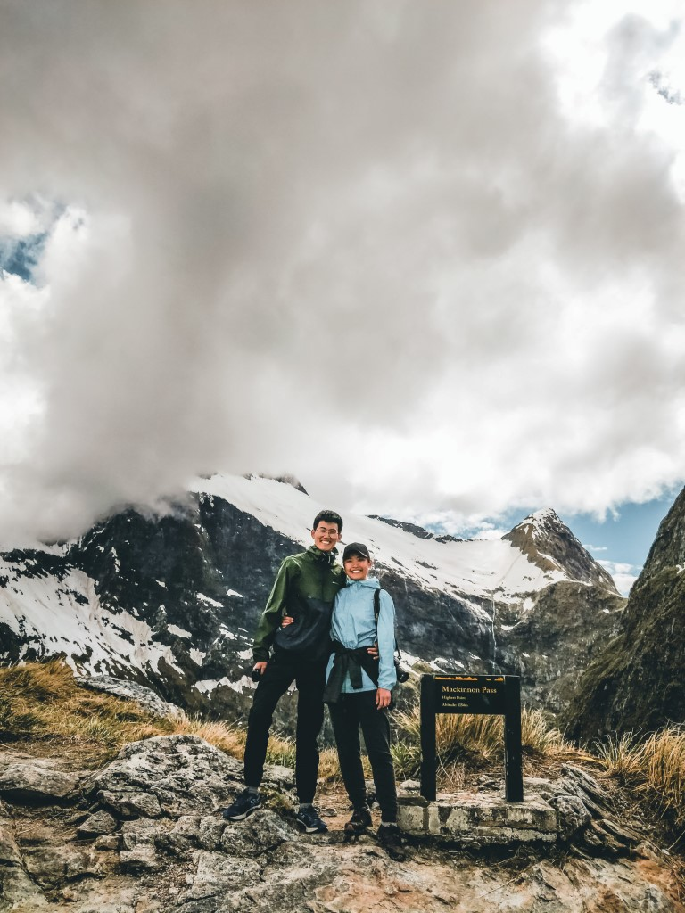 A couple posing with a sign and looming clouds above them