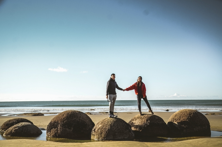 Couple standing on huge boulders whilst holding hands