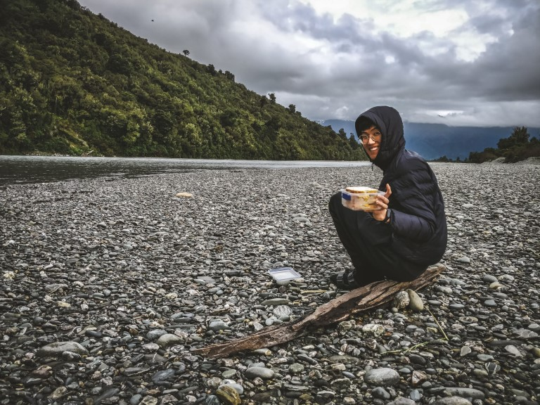 A man holding out his sandwich sitting on a driftwood smiling beside a rocky river