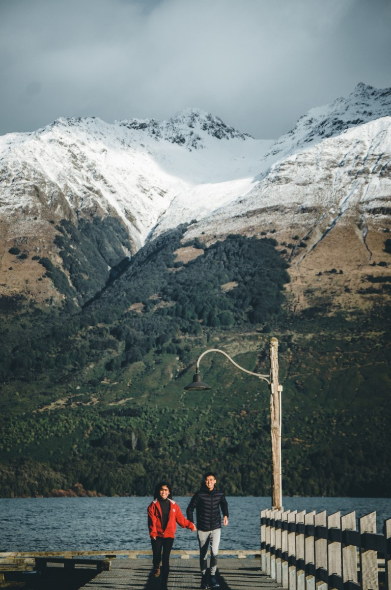 A couple running toward the camera with snowy mountains lined the back