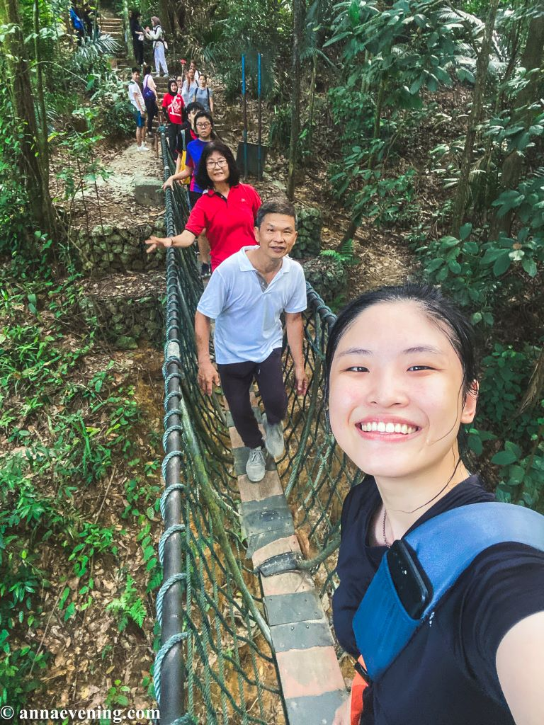 A selfie of five people while crossing a suspension bridge
