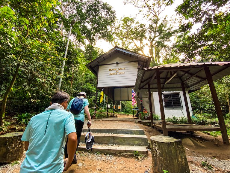 A blue-shirt couple walking toward a concrete building that says Gunung Datuk